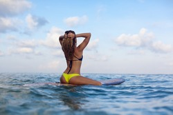 Happy girl in bikini have fun before surfing Surfer lie on surf board, look at sunset sky. People in water sport adventure camp, extreme activity on family summer beach vacation. Watersport background
