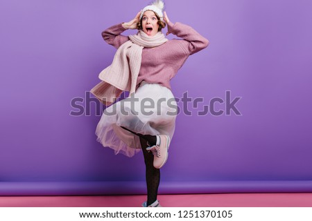 Happy girl in black pantyhose and purple sweater posing on one leg. Funny young woman in hat fooling around in studio and expressing positive emotions.