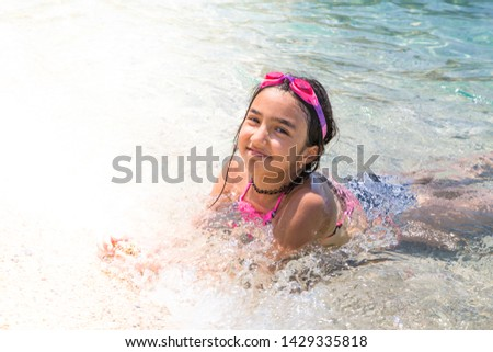 Happy girl in colorful swim wear and goggle, enjoying beach and sea,  splashing in water under sun light. Vacation for kids concept in resort area #1429335818
