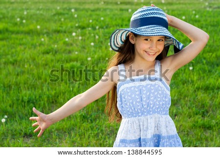 Happy girl in hat on the green meadow