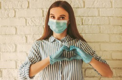 Happy girl in medical face mask and protective gloves gesturing heart symbol with hands. Young woman in protective face mask and medical gloves showing love sign with fingers. Health, customer care