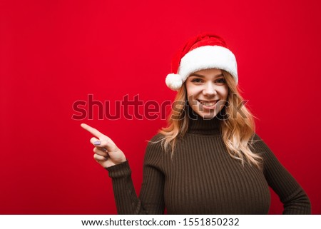 Happy girl in santa claus hat wearing hat stands on red background, wears warm sweater, shows thumbs up at copy space, looks into camera and smiles. New Year and Christmas concept