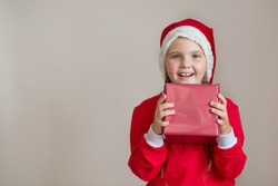 Happy girl in santa costume with gift on light gray background