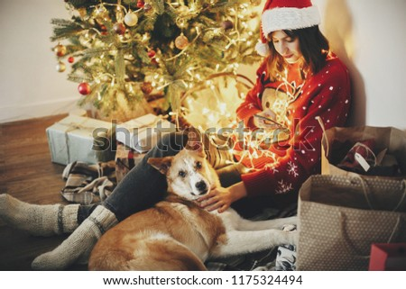 happy girl in santa hat holding phone and hugging dog under golden beautiful christmas tree with lights and presents in festive room. winter atmospheric  moments. happy holidays