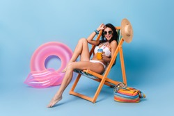 Happy girl in sunglasses and swimsuit drinking orange juice. Studio shot of tanned woman sitting on chaise longue on blue background.