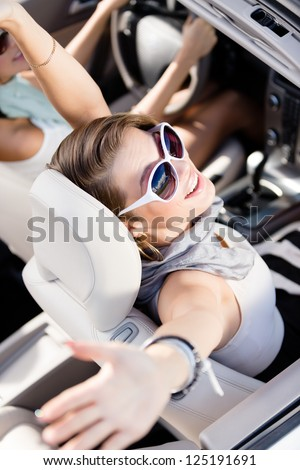 Happy girl in the car with her hands up. Having fun while driving the car