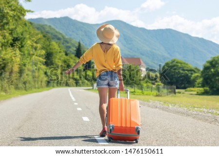Happy girl in the summer goes on vacation, on vacation with an orange suitcase on the background of nature and mountains. The concept of travel, weekend in a beautiful place, a house in the mountains