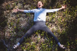 Happy girl in warm sweater and tights spread her legs and arms to the side screaming with her mouth open on moss in pine forest
