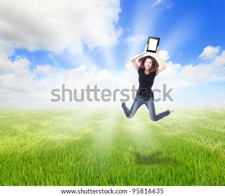 Happy Girl Jump and show touch pad computer on the meadow with blue sky and white cloud, for cloud computing concept