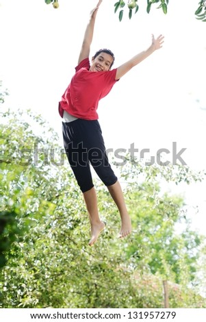Happy girl jumping high in nature surrounded by trees