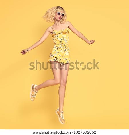 Happy girl Jumping in Studio on Yellow background. Blond Slim Model Having Fun in Fashionable Sunglasses, Trendy Summer Playsuit. Young Playful Beautiful woman in Stylish Outfit #1027592062