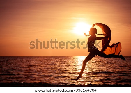 Happy girl jumping on the beach at the sunset time #338164904