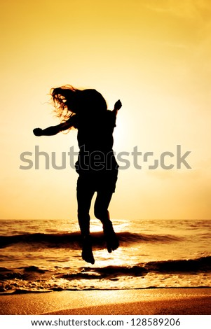 Happy girl jumping on the beach in sunset time