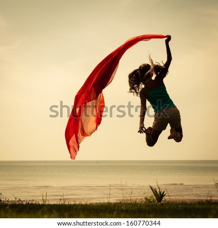 Happy girl jumping on the beach on the day time - stock photo