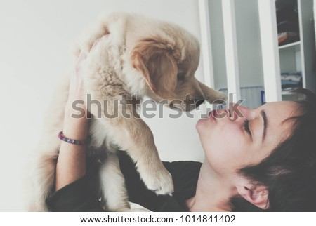 Happy girl kissing her new golden retriever puppy and holding him in her arms. #1014841402