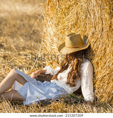 Happy girl lies on field relaxing and enjoy the nature on a summer evening. Free people concept