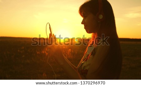 happy girl listening to music and dancing in the rays of beautiful sunset. young girl in headphones and with a smartphone touches finger to the sensor of tablet selects songs online. Slow motion. #1370296970