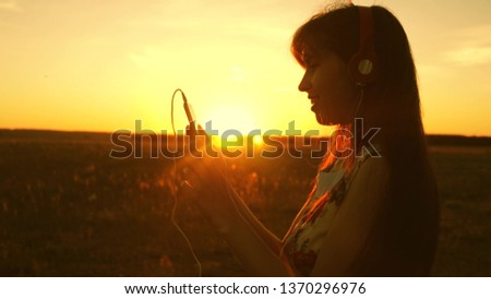 happy girl listening to music and dancing in the rays of beautiful sunset. young girl in headphones and with a smartphone touches finger to the sensor of tablet selects songs online. Slow motion. #1370296976