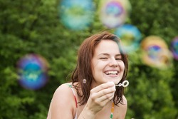 Happy girl making soap bubbles against trees