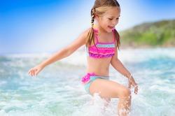 happy girl on a  tropical beach ocean has a fun with splash