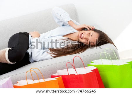 Happy girl on couch talking on mobile phone in front of shopping bags.