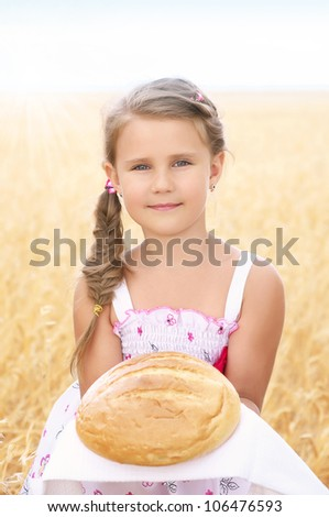 happy girl on field of wheat with bread