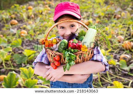 Happy girl on pumpkin's field with basket of vegetables