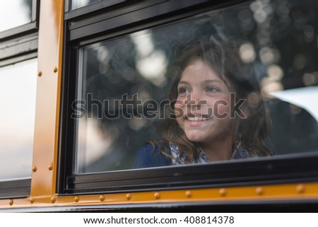 Happy girl on school bus excited for first day of class