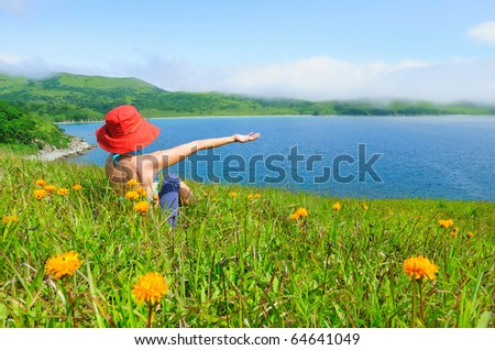 happy girl on the flower meadow against the sea landscape