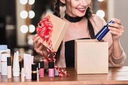 Happy girl opening present box with cosmetics
