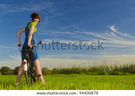 Happy girl over a bicycle and looking back, in a green meadow