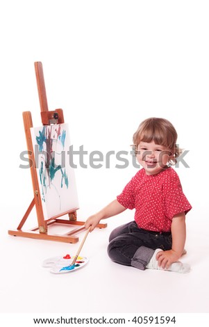 Happy girl painting on easel