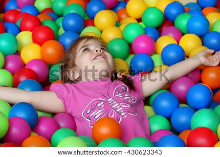 Happy girl playing and having fun at kindergarten with colorful balls, family weekend concept, happy birthday and merry party #430623343