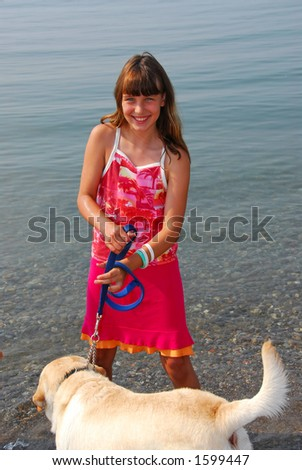 Happy girl playing with her dog in water