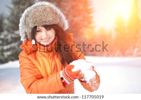 Happy girl playing with snow in the winter landscape