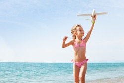 Happy girl playing with toy plane on the seashore