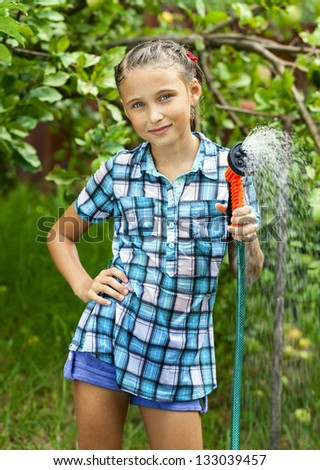 Happy girl pours water from hose, watering  flowers and grass