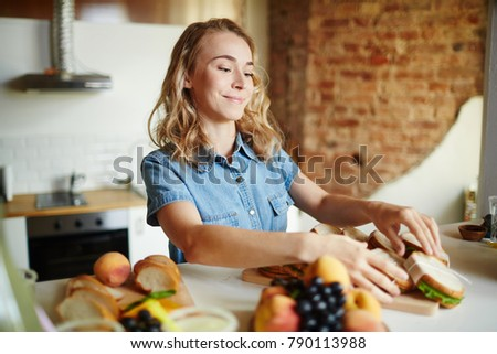 Happy girl preparing sandwiches for her guests at home