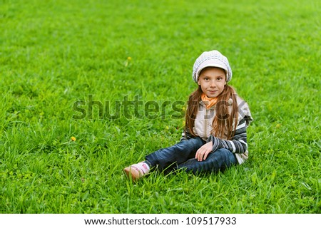 Happy girl-preschooler on green grass in spring city park.
