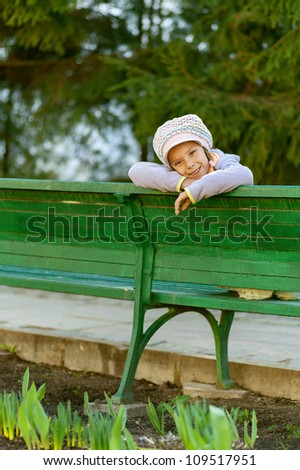 Happy girl-preschooler sitting on green bench in city park.