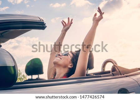 Happy girl relaxing enjoying sunshine sitting in convertible car on summer road trip vacation driving away on travel. Freedom concept woman feeling free raised his hands to top. riding with the wind.