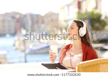 Happy girl relaxing in a coffee shop listening to music with headphones and a tablet on vacation #1177102630