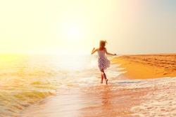 Happy girl running on the beach towards the sun