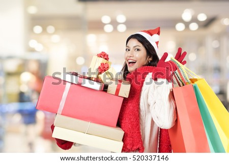 Happy girl shopping christmas gifts in shopping mall. Christmas shopping idea concept.
