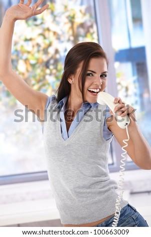 Happy girl singing to receiver, having fun, laughing.
