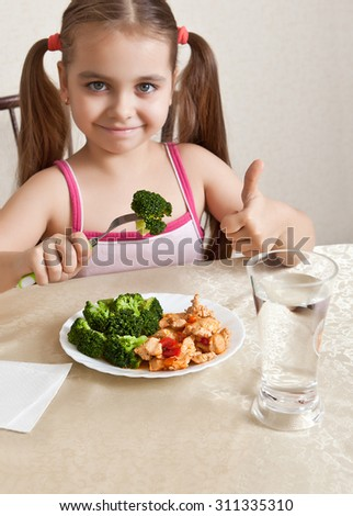 Happy girl sitting at the table and shows the thumb #311335310