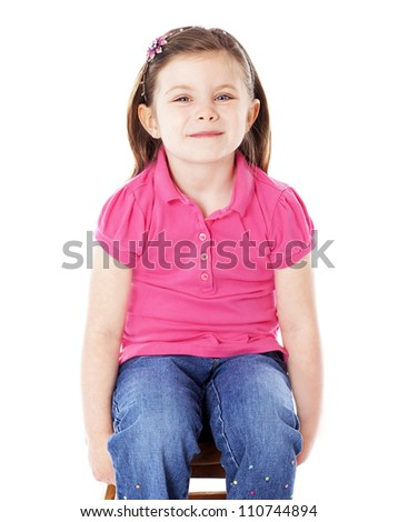 Happy girl sitting on a stool isolated on white