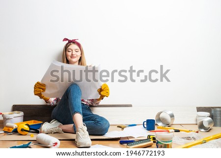 Happy girl sitting on floor with paper blueprint. Home remodeling after moving. Construction tools and materials for building. Young woman wearing checkered shirt and jeans redesigning her home. Foto stock ©