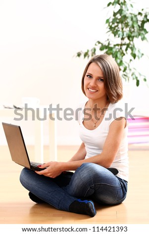 Happy girl sitting on the floor at home with laptop