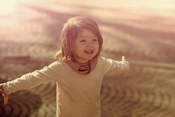Happy girl smile with open hand gesture on sunny day on grey pavement outdoor. Child, innocence, childhood concept.
